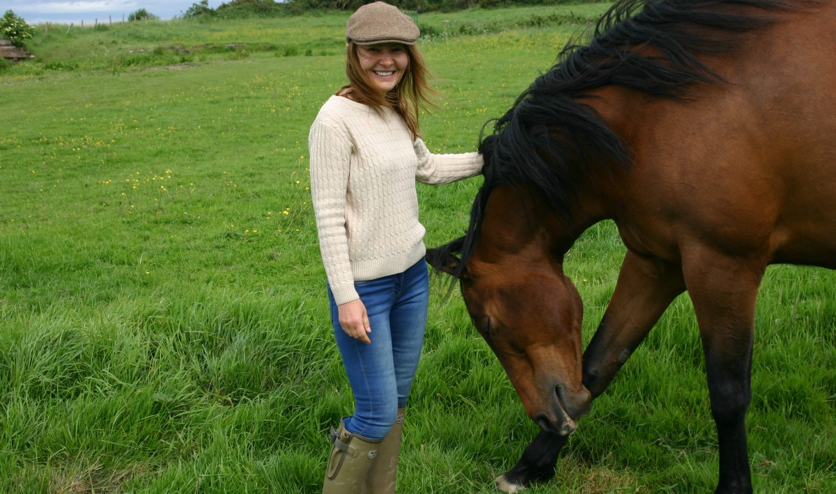 Standing with horse in field