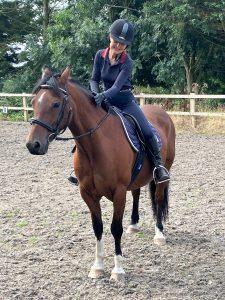 happy rider patting horse in praise